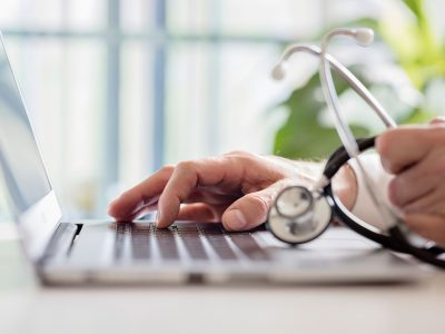 doctor-entering-patient-notes-on-laptop-in-BTUDVEL